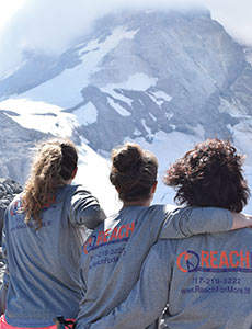 Trio of women wearing Reach Fitness hoodies sitting atop a mountain staring out over Mt. Hood.